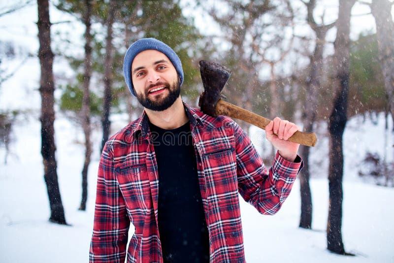 Skäggig hipsterman i en snöig skog för vinter med yxan på en skuldra Skogsarbetareanseende i skogmankontrollen fotografering för bildbyråer