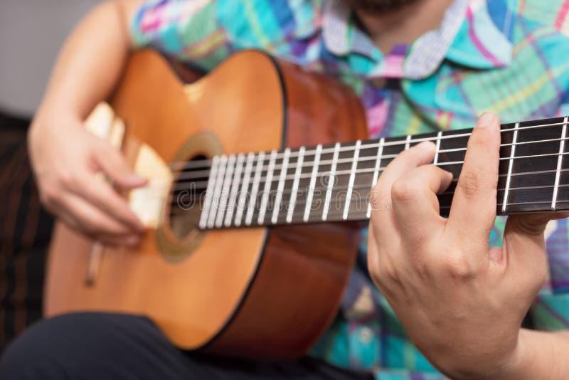 Skäggig hipstermanhand som spelar den akustiska gitarren Selektiv fokus för närbild förestående fotografering för bildbyråer