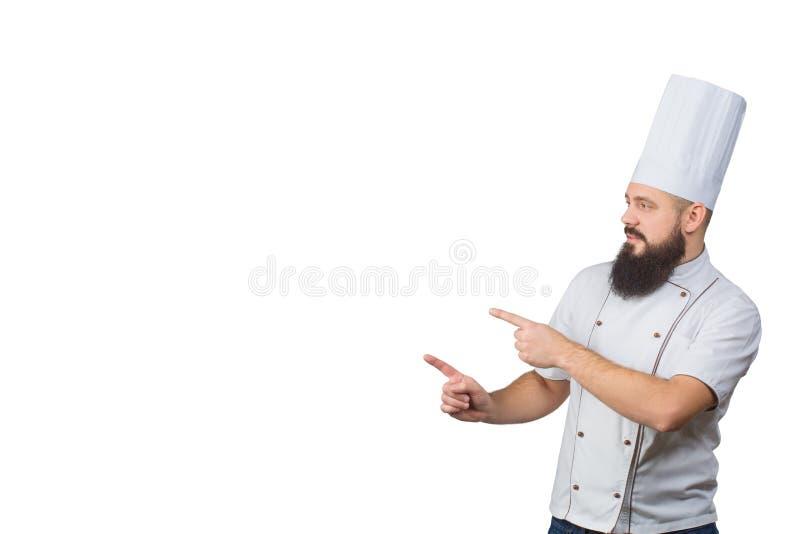 Skäggig kockkock som pekar med hans fingrar som isoleras på vit bakgrund, kopieringsutrymme på sida arkivfoton