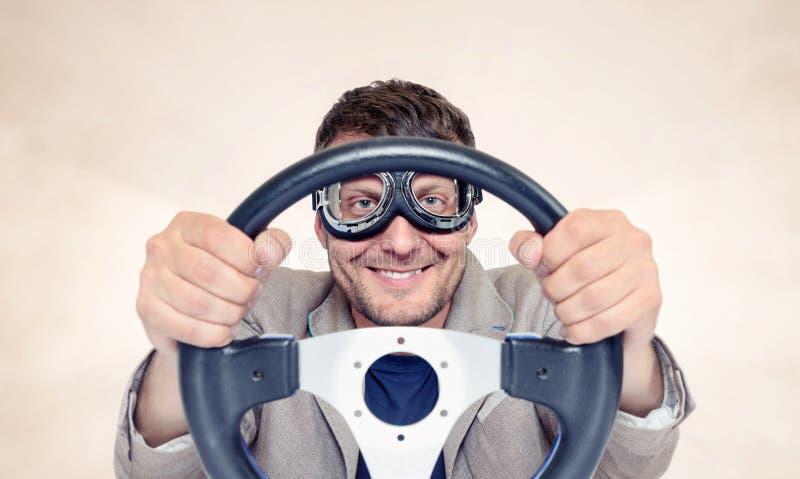 Skäggig lycklig man i stilfull skyddsglasögon med styrninghjulet på bakgrund, begrepp för bilchaufför royaltyfri foto