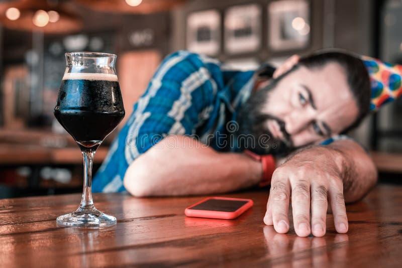 Skäggig mörkhårig man som ser exponeringsglas av trevligt kallt mörkt öl royaltyfri fotografi