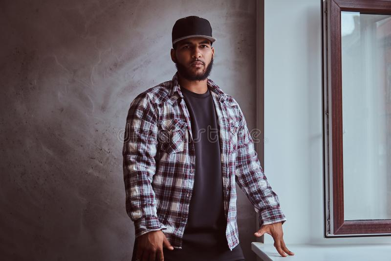 Skäggig man för afrikansk amerikan som bär ett rutigt skjorta- och lockanseende bredvid fönsterfönsterbräda royaltyfria bilder