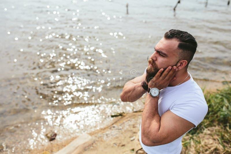 Skäggig man för amerikan som trycker på hans skägg fotografering för bildbyråer