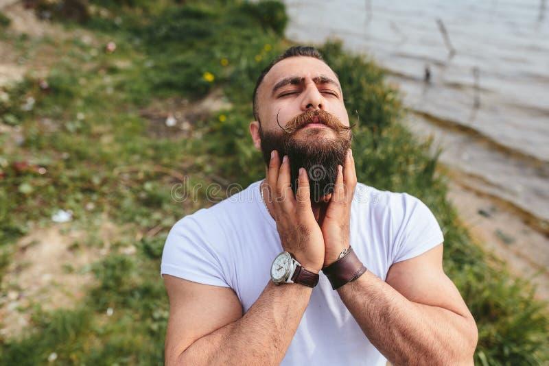 Skäggig man för amerikan som trycker på hans skägg arkivbilder
