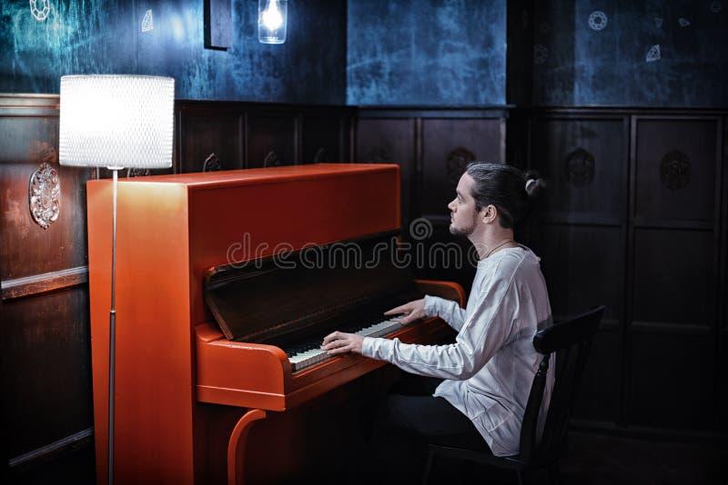 Skäggig man för barn som spelar det röda pianot royaltyfria foton