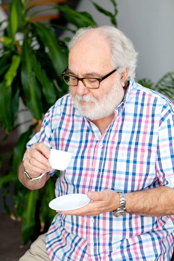 Skäggig man för pensionär som dricker kaffe fotografering för bildbyråer