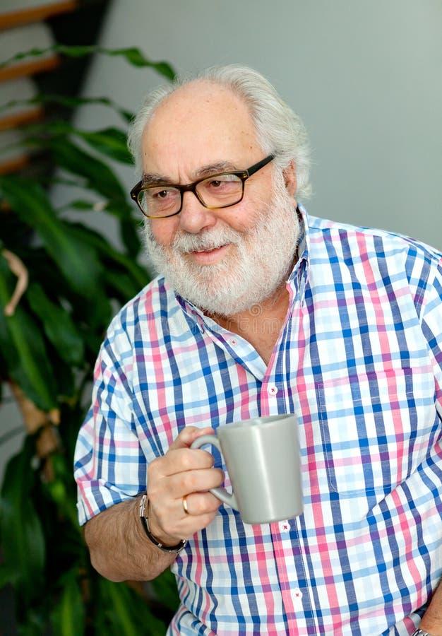 Skäggig man för pensionär som dricker kaffe arkivbild