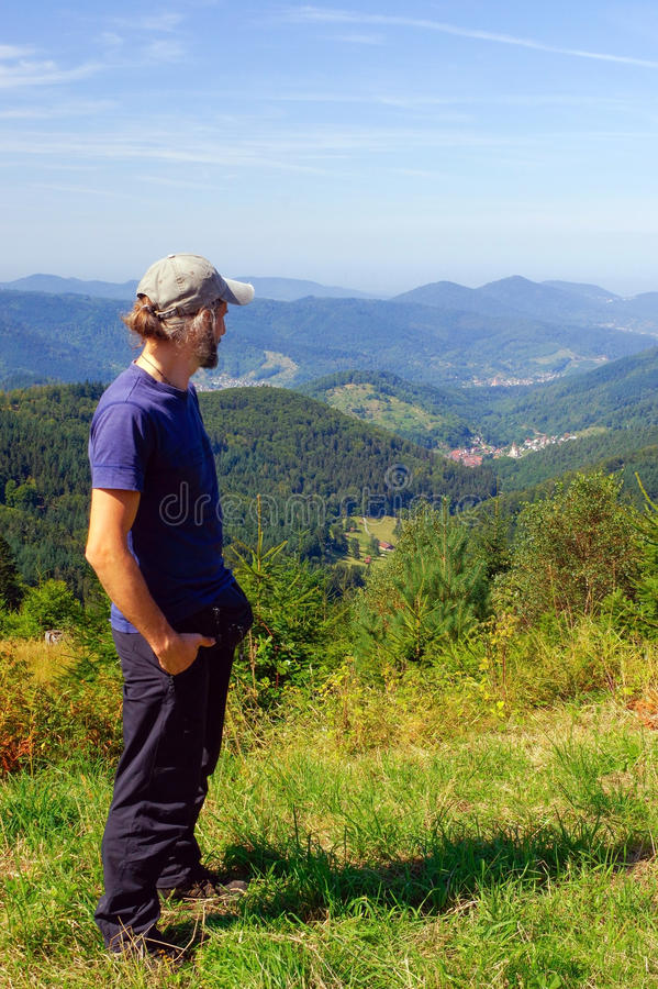 Skäggig man, fotvandrare och att stå i bergen och blickarna in i avståndet tillbaka sikt solig dag royaltyfria bilder