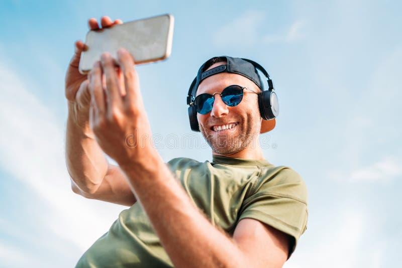Skäggig man i baseballmössa, trådlös hörlurar och gladlynt le för blå solglasögon ta använda för selfiebild som är modernt royaltyfri bild
