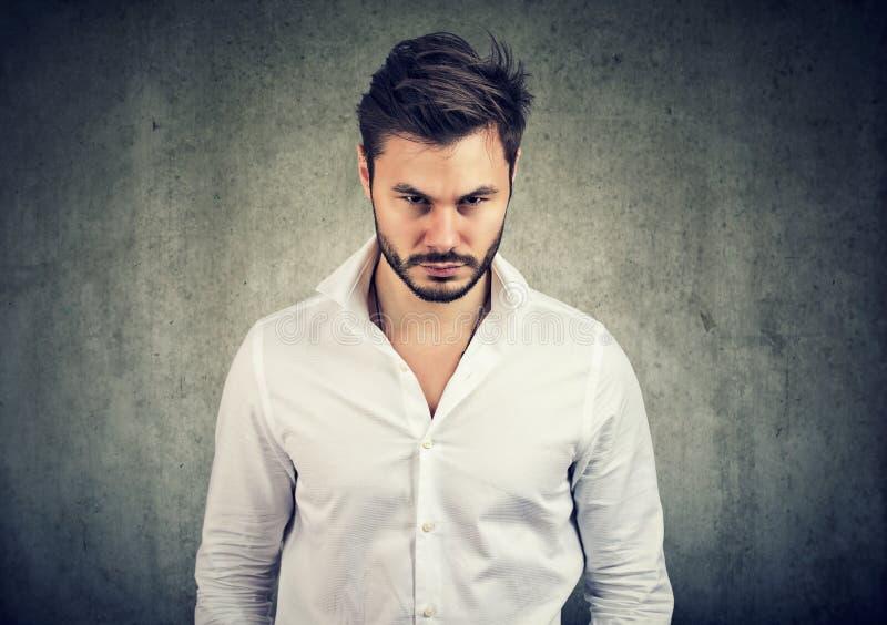 Skäggig man i den vita skjortan som ser med ilska och anstöt på kameran på grå bakgrund arkivfoton
