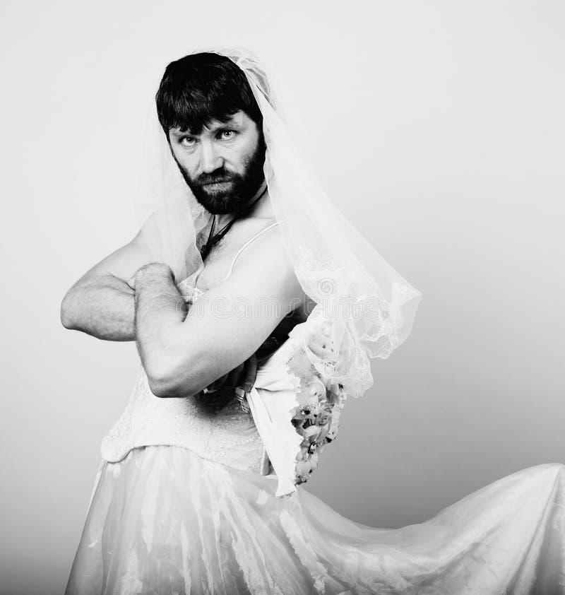Skäggig man i en kvinnas bröllopsklänning på hennes nakna kropp som rymmer en blomma rolig skäggig brud som är svartvit arkivbild