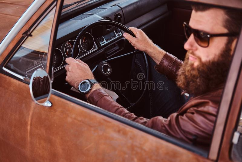 Skäggig man i för bruntläder för solglasögon som det iklädda omslaget kör en retro bil arkivbild