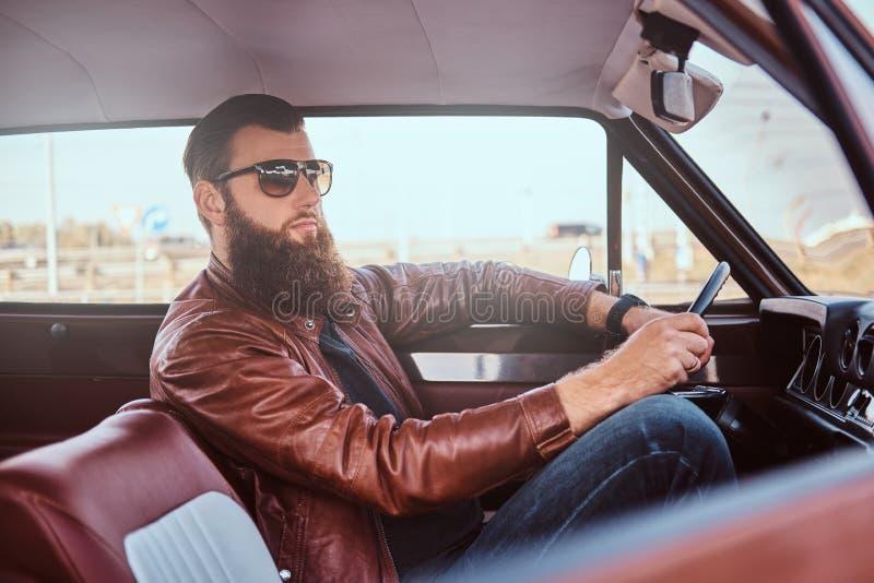 Skäggig man i för bruntläder för solglasögon som det iklädda omslaget kör en retro bil royaltyfria bilder
