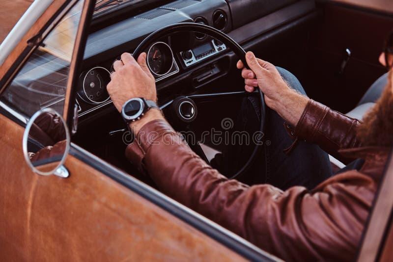 Skäggig man i för bruntläder för solglasögon som det iklädda omslaget kör en retro bil royaltyfri foto