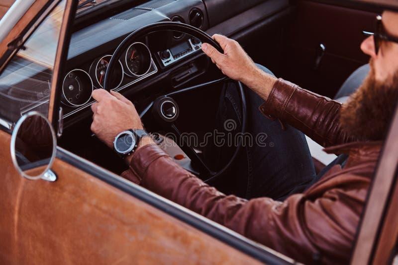 Skäggig man i för bruntläder för solglasögon som det iklädda omslaget kör en retro bil arkivbilder