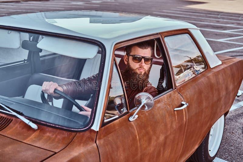 Skäggig man i för bruntläder för solglasögon som det iklädda omslaget kör en retro bil royaltyfri fotografi