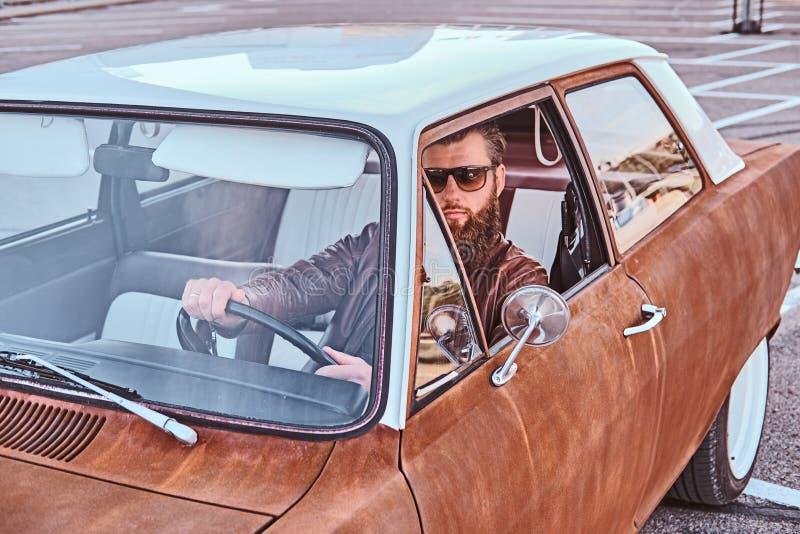 Skäggig man i för bruntläder för solglasögon som det iklädda omslaget kör en retro bil fotografering för bildbyråer