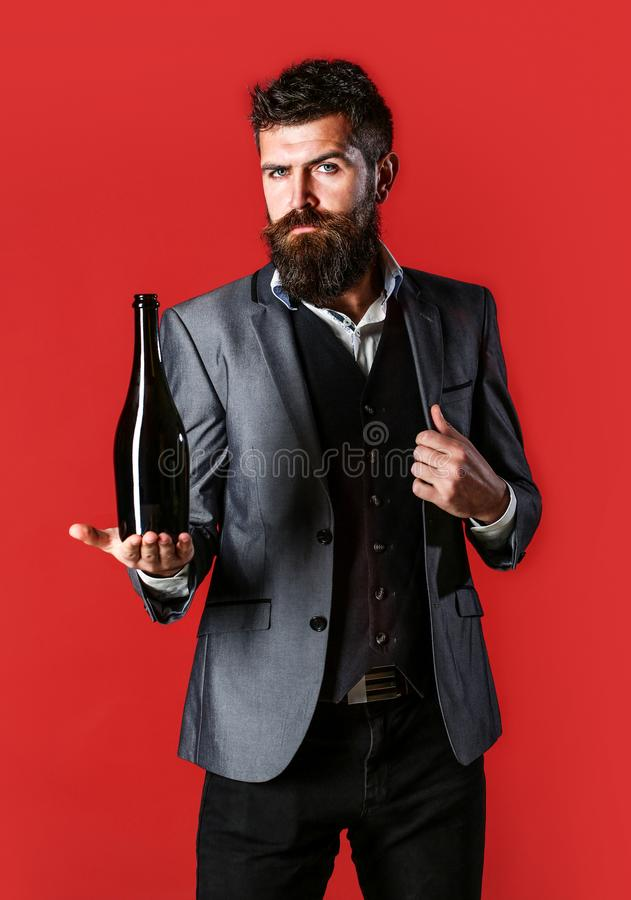 Skäggig man med en flaskchampagne av och ett exponeringsglas Stilfull man i smokingen, dräkt, omslag Maninnehavflaska med royaltyfri fotografi