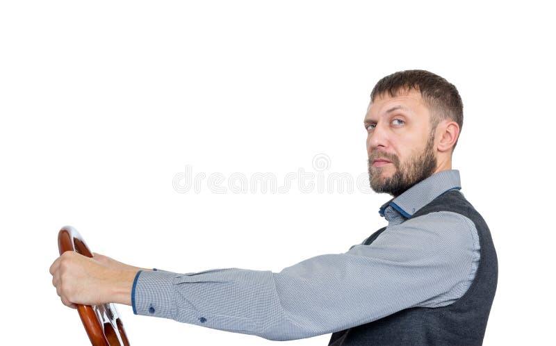 Skäggig man med ett styrninghjul, sidosikt som isoleras på vit bakgrund Bildrevbegrepp royaltyfri foto