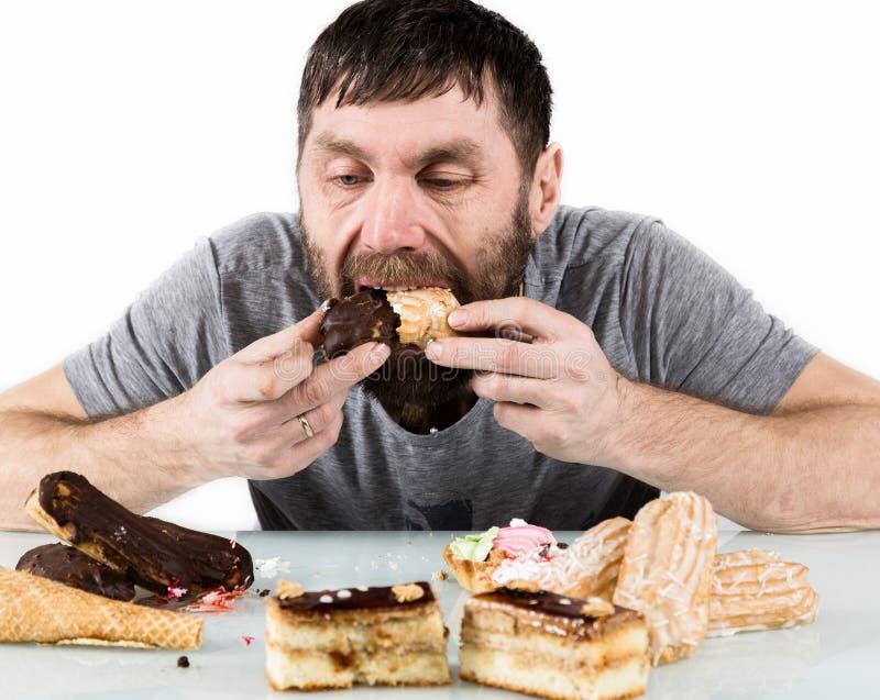Skäggig man som äter muffin med nöje efter en banta skadlig men läcker mat arkivfoto