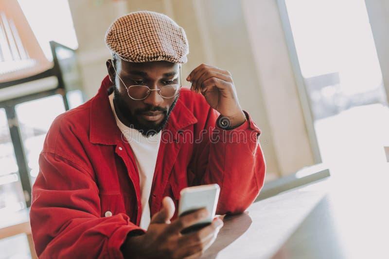 Skäggig man som bara sitter och ser skärmen av hans smartphone royaltyfri foto