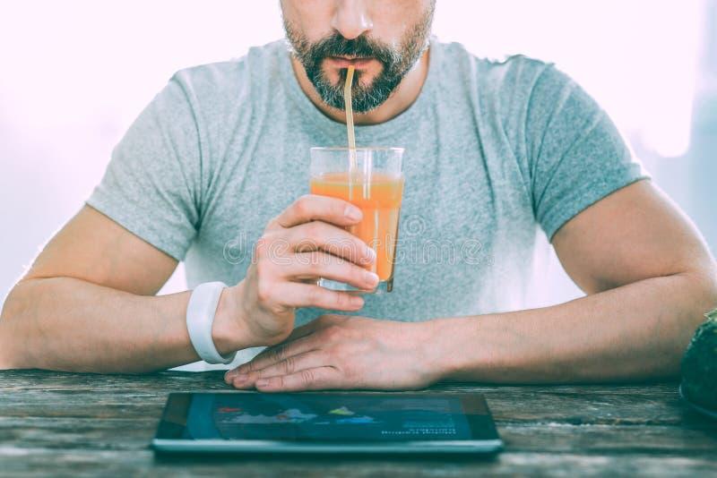 Skäggig man som dricker ny kall orange fruktsaft arkivbild