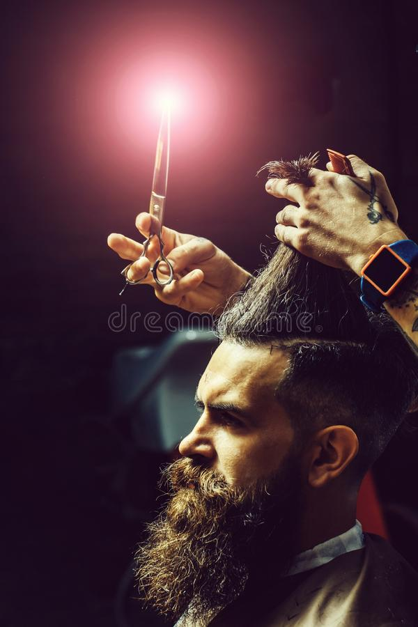 Skäggig man som får stilfullt hårklipp med sax fotografering för bildbyråer