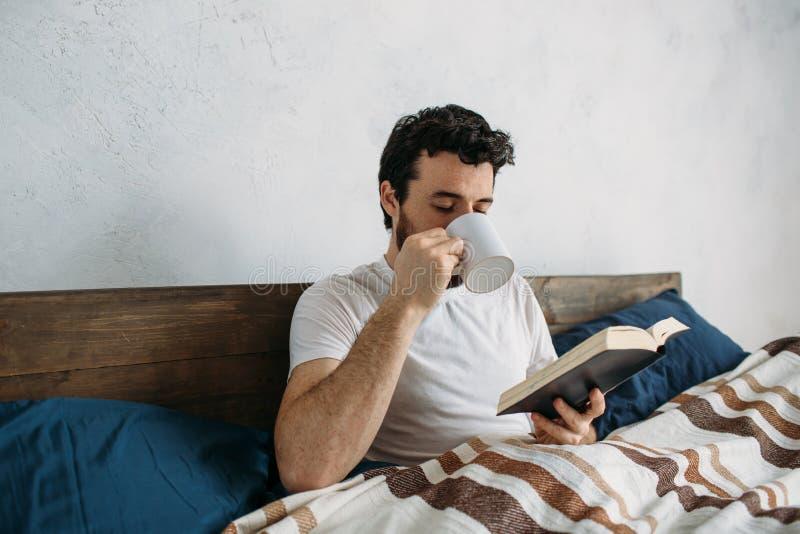 Skäggig man som läser en stor bok som ligger i hans sovrum royaltyfria foton