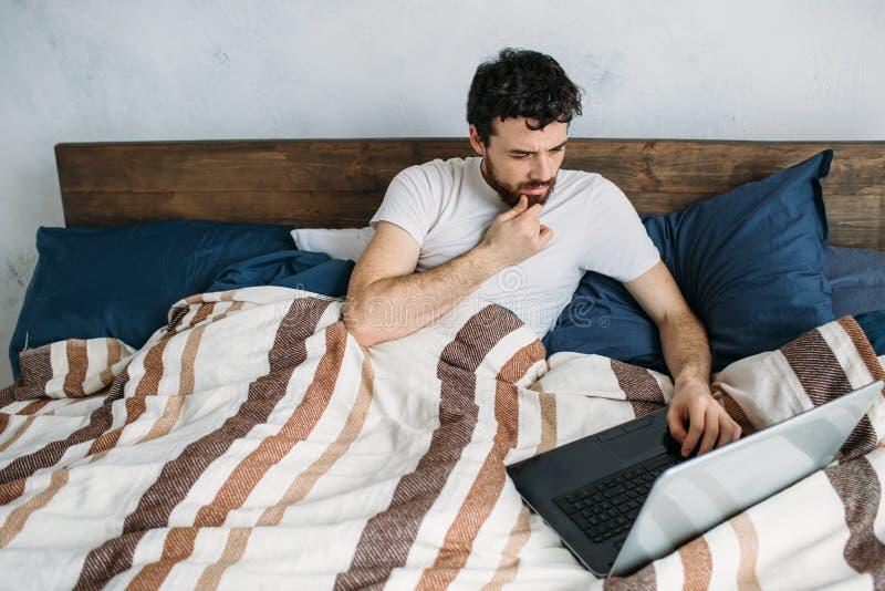 Skäggig man som ligger i morgonsäng med bärbara datorn royaltyfria foton