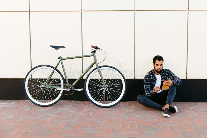 Skäggig man som sitter med minnestavlan nära cykeln, utomhus arkivbild