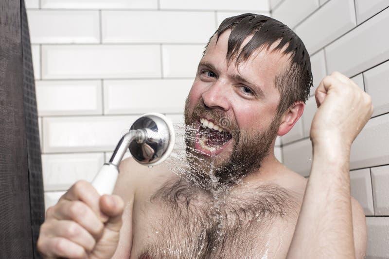 Skäggig man som sjunger i badrummet genom att använda duschhuvudet med f royaltyfri bild