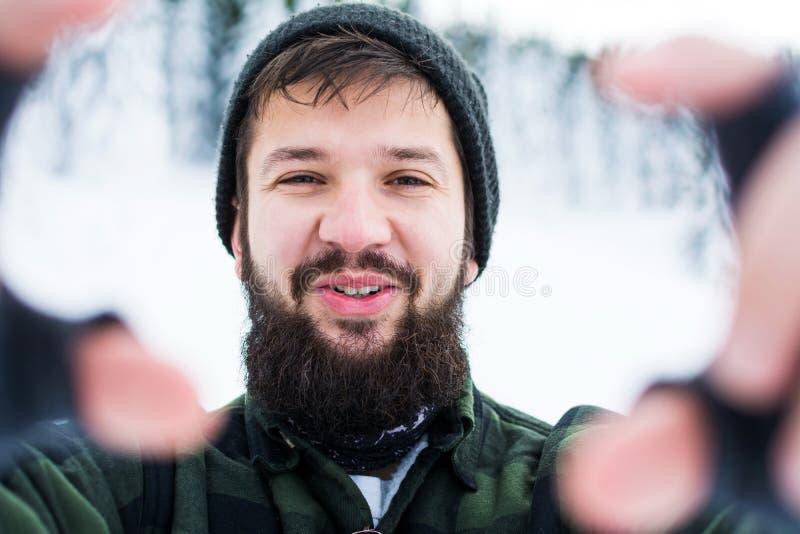 Skäggig man som tar selfie på det snöig berget royaltyfria bilder