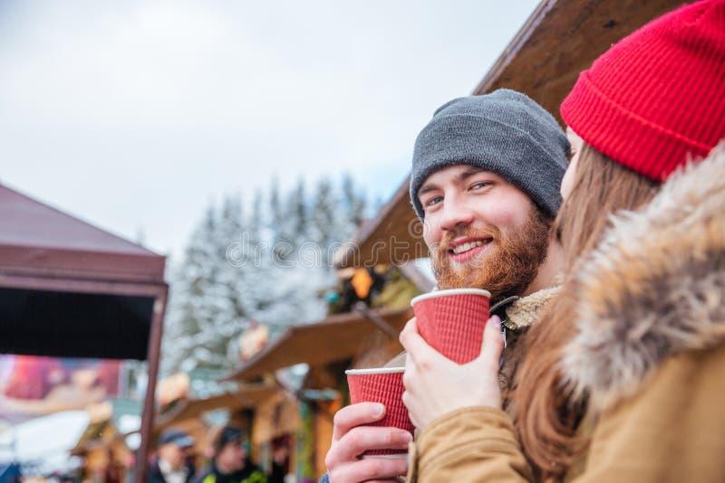 Skäggig man som utomhus dricker kaffe med hans flickvän arkivfoto