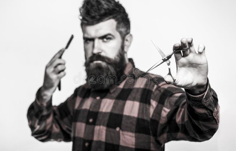 Skäggig man, skäggig man Stående av det stilfulla manskägget Barberaresaxen och den raka rakkniven, barberare shoppar Tappning royaltyfri bild