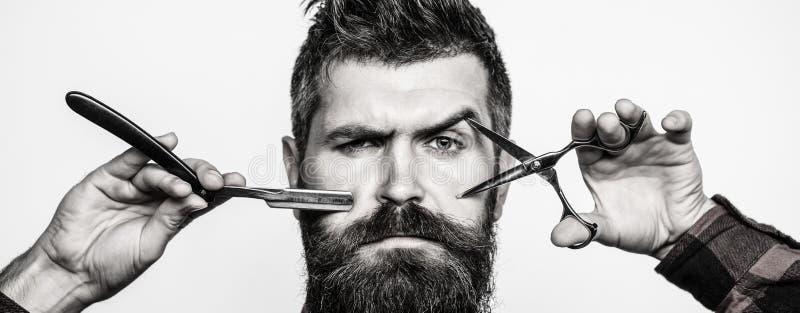 Skäggig man, skäggig man Stående av det stilfulla manskägget Barberaresaxen och den raka rakkniven, barberare shoppar Tappning arkivbilder