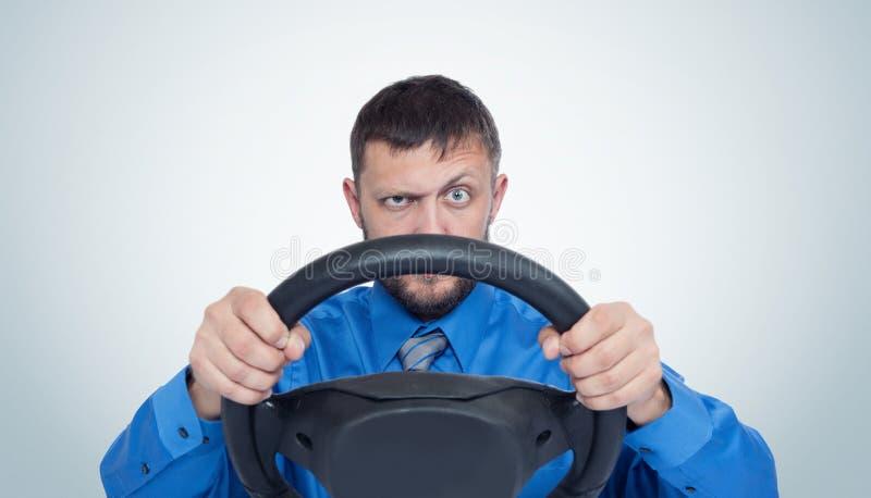 Skäggig manchaufför med ett styrninghjul, auto begrepp royaltyfria bilder