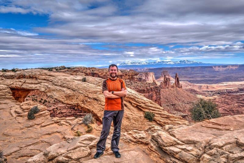 Skäggig manhipster som ler på klippan med kanjonsikter royaltyfri fotografi
