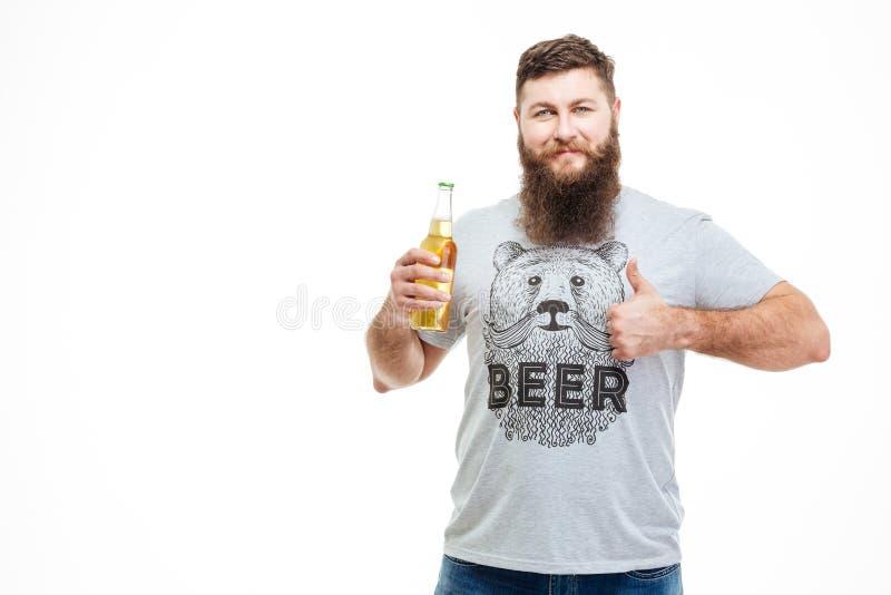 Skäggig maninnehavflaska av öl- och visningtummar upp royaltyfri foto