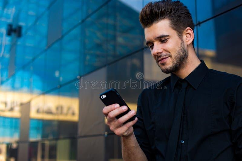 Skäggig manlig bankir som läser mejl på smartphonen royaltyfria foton