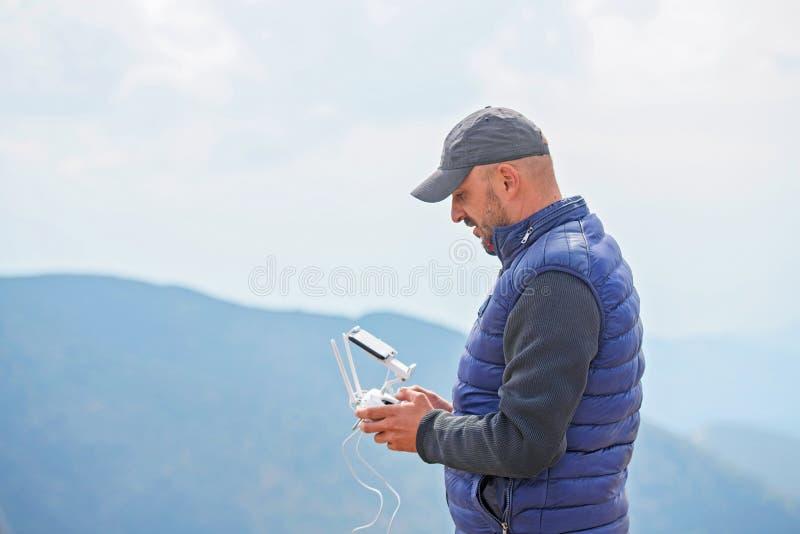 Skäggig manlig fjärrkontroll för modellbrukssurr som flyger apparaten i luft Manfungerande surrflyg i natur ny teknik royaltyfri bild