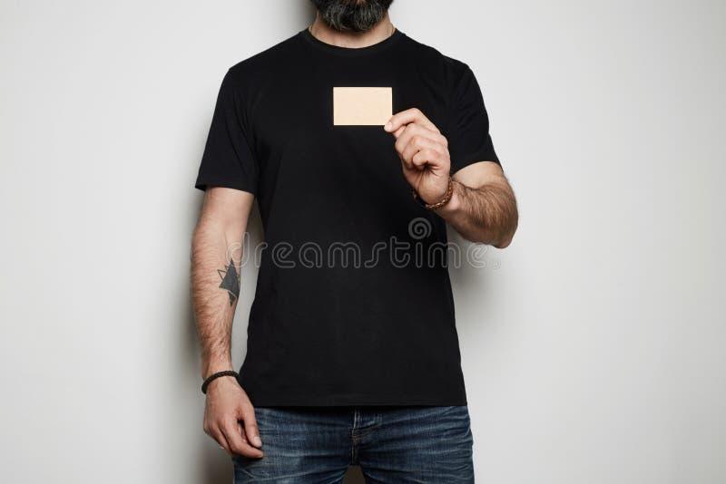 Skäggig manlig modell som ger hand det tomma svarta affärskortet på suddig bakgrund Tom annonsering för modellkopieringsdeg royaltyfri bild