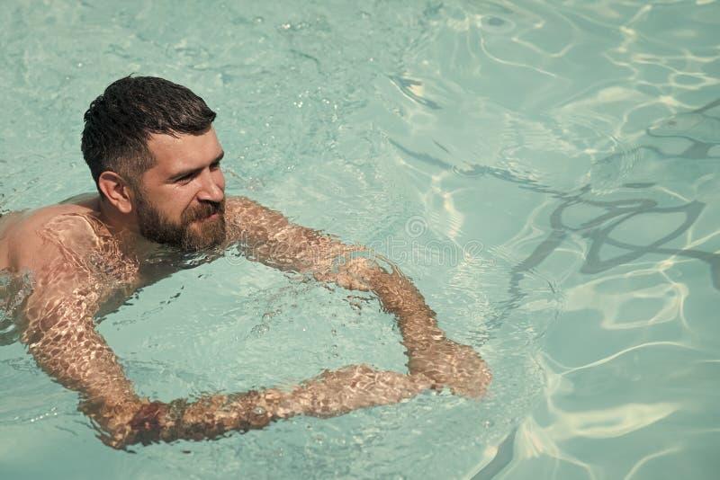 Skäggig mansimning i blått vatten Sommarsemester och lopp till havet Koppla av i brunnsortsimbassängen, uppfriskning och royaltyfri fotografi