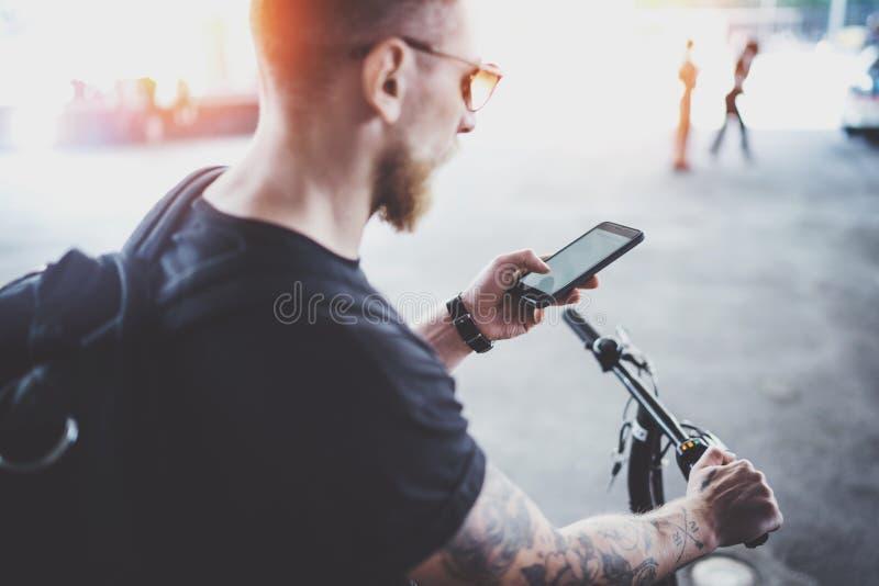 Skäggig muskulös tatuerad hipster i solglasögon genom att använda smartphonen, når att ha ridit med den elektriska sparkcykeln i  royaltyfri bild