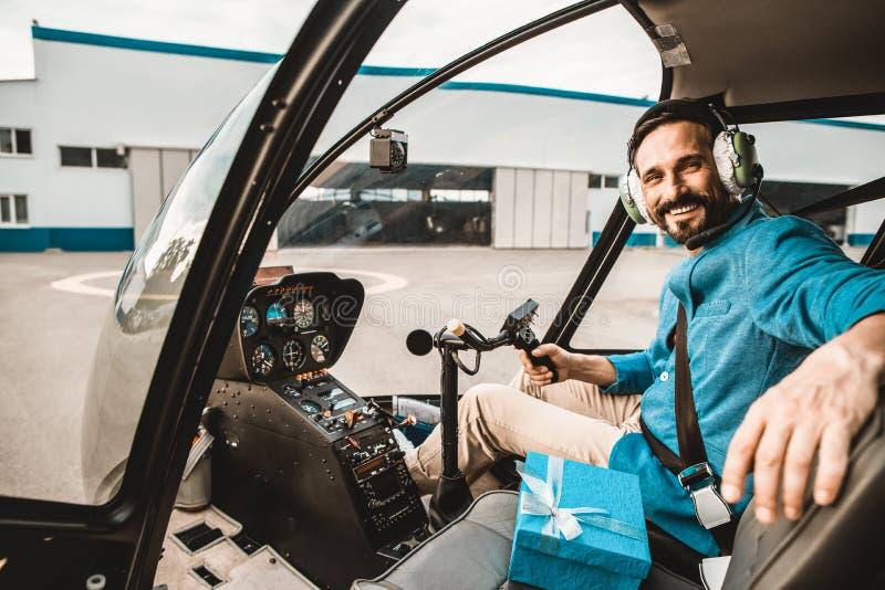 Skäggig pilot som ler och ser dig från helikopterkabinen royaltyfria bilder