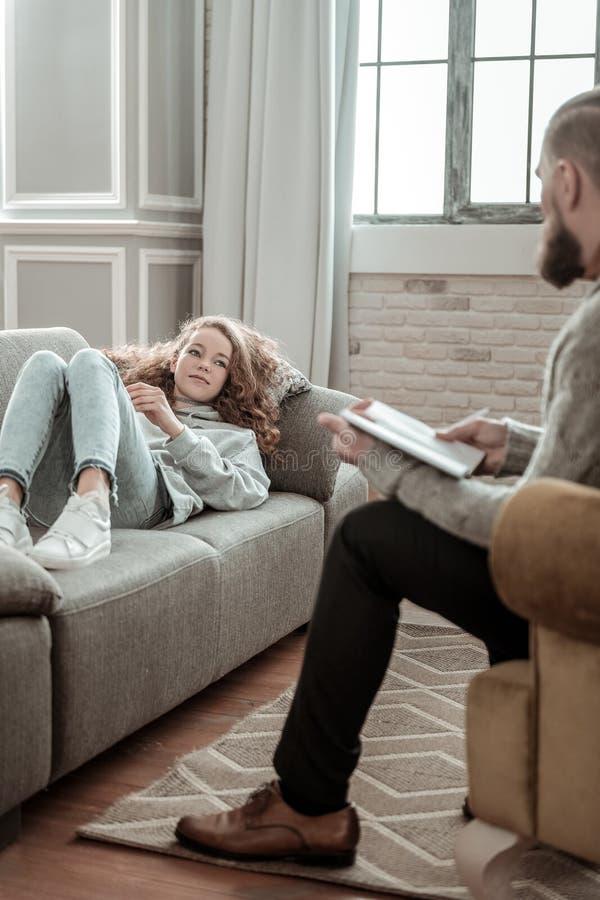 Skäggig privat terapeut som lyssnar till flickan som delar hennes tankar royaltyfria foton