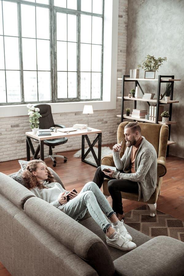 Skäggig privat terapeut som sitter och lyssnar till den tonårs- flickan fotografering för bildbyråer