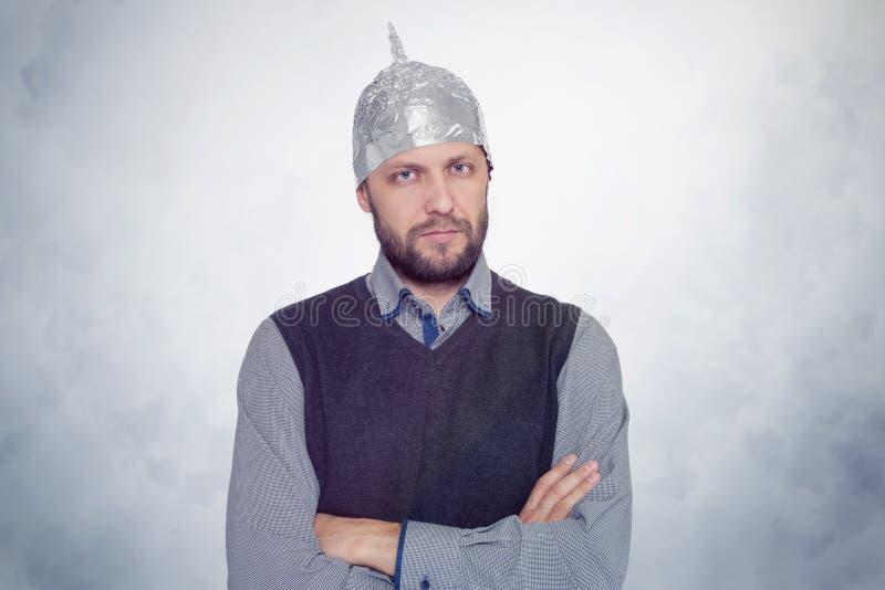 Skäggig rolig man i ett lock av aluminum folie Begreppskonstfobin arkivfoto