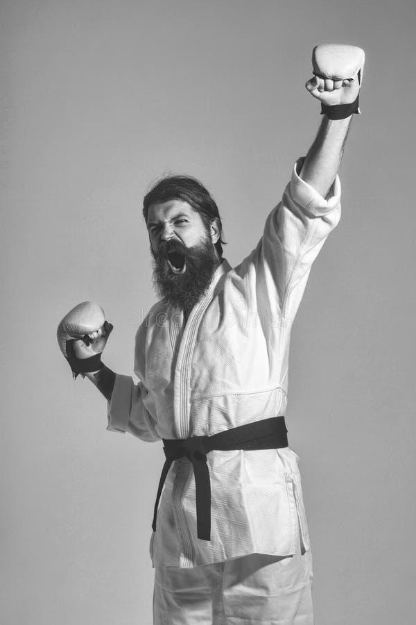 Skäggig ropa lycklig karateman i kimono- och boxninghandskar fotografering för bildbyråer