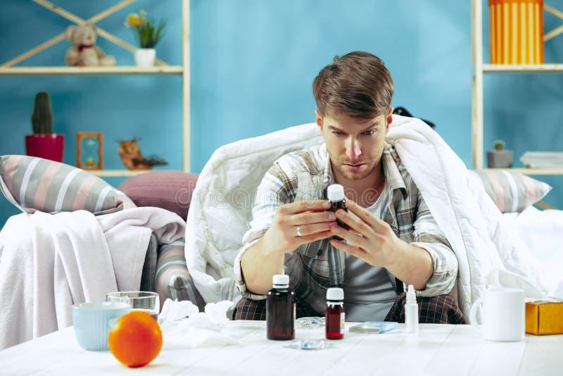 Skäggig sjuk man med rökkanalen som hemma sitter på soffan Sjukdomen influensa, smärtar begrepp home avkoppling Sjukvård arkivbild