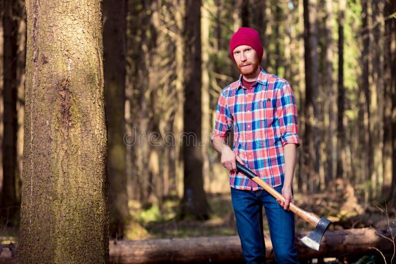 Skäggig skogsarbetare i en rutig skjorta med en yxa som står nära en t royaltyfria foton